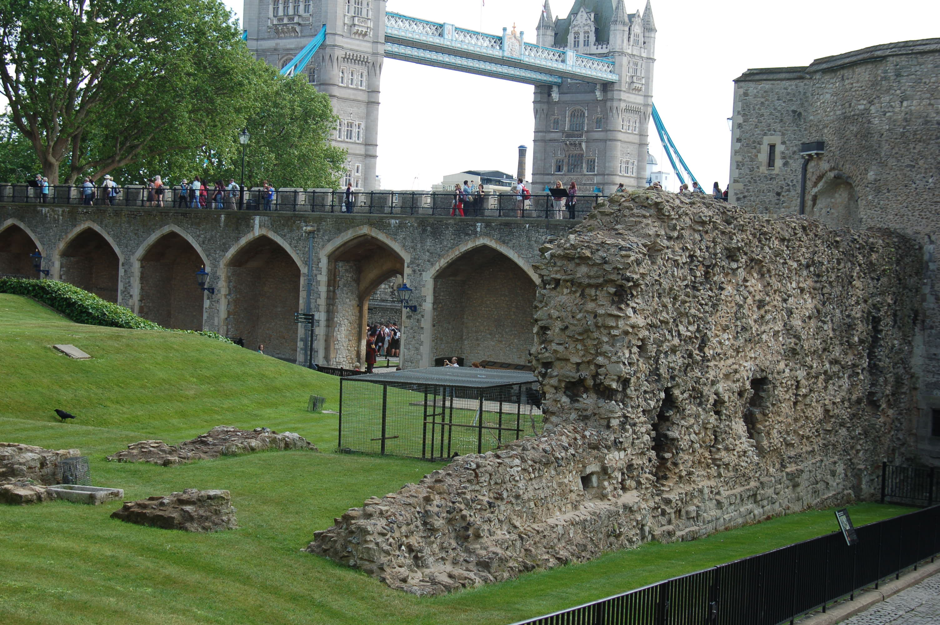 original Roman Wall of Tower of London with tower bridge in the background