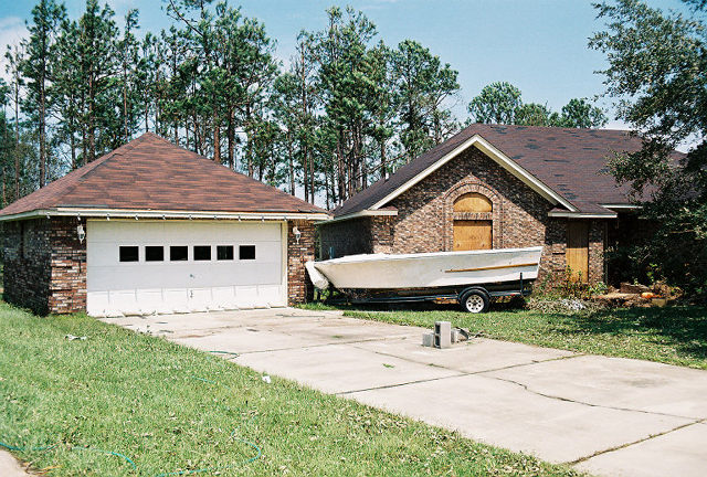Our house after Hurricane Katrina, with my project boat washed into the planter bed.